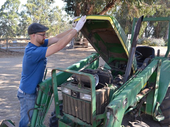 Pull the hood release latch at the front right of the tractor and lift the hood up.
