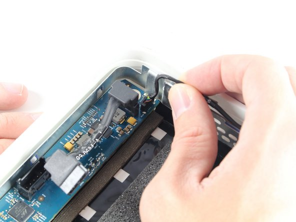Remove the LED cable from the top left corner of the logic board by pulling the cable straight out and away from the board.
