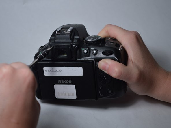 Image 3/3: Remove the three 7mm screws around the viewfinder.