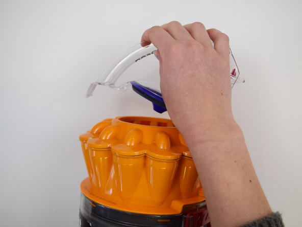 Image 1/3: Lift up the clear handle to reveal the main cylindrical filter. Pull out the purple filter piece to replace.