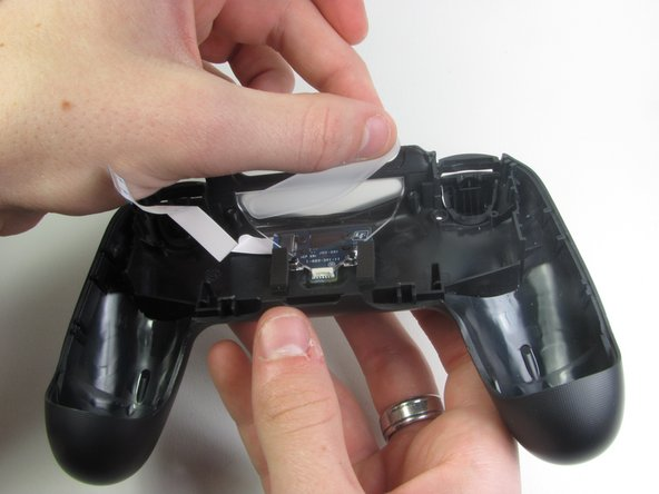 Keep the clear plastic piece on the controller, but keep it pushed down to provide room for charger port replacement.