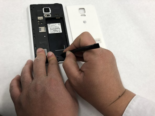 Use a Spudger to remove the battery using the notch located underneath the battery.