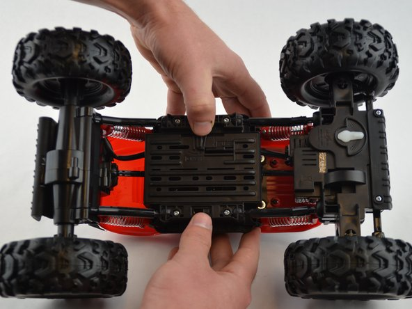 Start by flipping the R/C truck over.