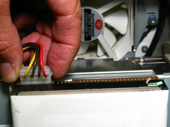 Image 2/2: Disconnect the Hard Drive's Data and Power Cables, Pulling the Data Cable connector by its white plastic tab (not the cable itself), and the Power Cable by its outside edges. These connectors can be very tight. Don't get discouraged. Patiently wiggle them back and forth so that they release evenly to avoid bending any pins.