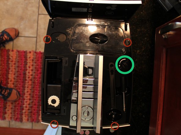 Five screws labeled with the red circles need to be removed before the top can be taken off. One under each of the left and right top hinged covers, two under the top back cover and of the two under the ground coffee top door, the one nearest the water tank (the other one holds the chrome plastic to the top).