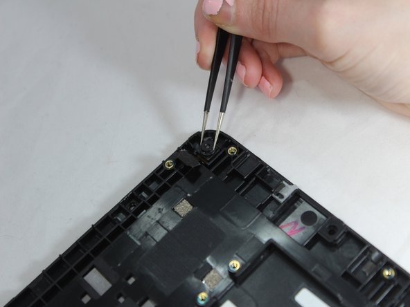 Use tweezers to grab the camera's edges and gently lift the camera up from tablet backing.