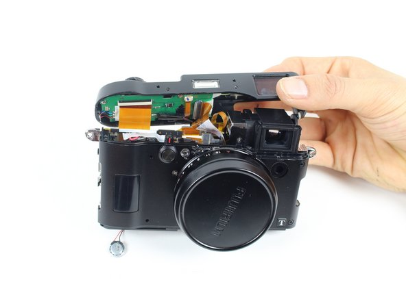 Remove the top frame by lifting it off and pulling it towards the backside of the camera.