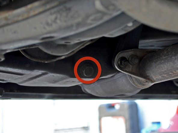 Locate the 17 mm hex oil drain plug. It is on the driver's side of the car facing backwards.