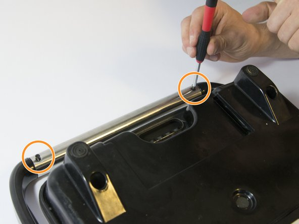 Place the toaster upside down and remove the two Phillips screws on either side of the handlebar.