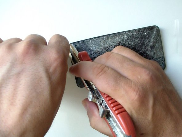 Image 1/2: Use a hot gun or hair dryer and warm the glass to soften the adhesive.