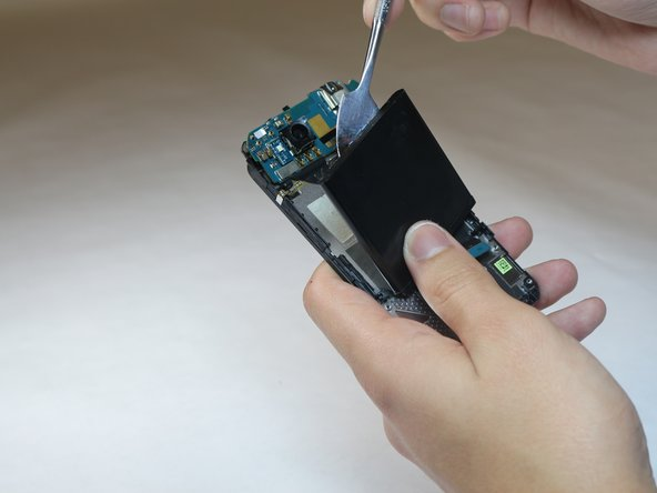 Image 3/3: Use a metal spudger to remove the battery.