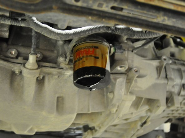 Image 2/3: Oil will begin to run down the sides of the oil filter. It is up to your discretion to either let it drain slowly this way or take the filter off quickly. Keep in mind that no matter what, the filter itself will still have oil in it that must be drained.