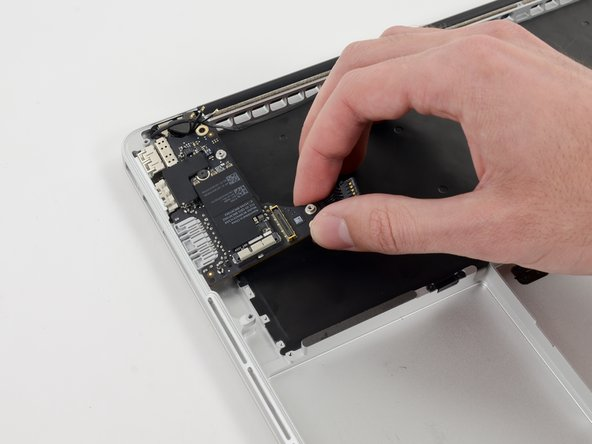 Image 1/2: Carefully pull and remove the I/O board away from its recess in the upper case.
