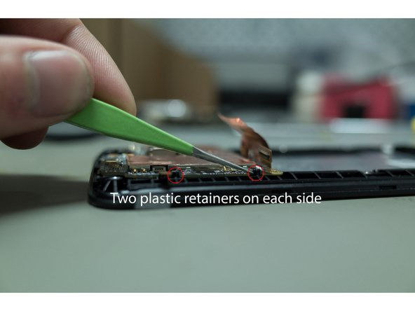 There are four plastic retainers which fix the remaining unit to the body of the phone. Use a small amount of force on one side to pop this section out. Once this is freed, it should be simple to remove it completely.