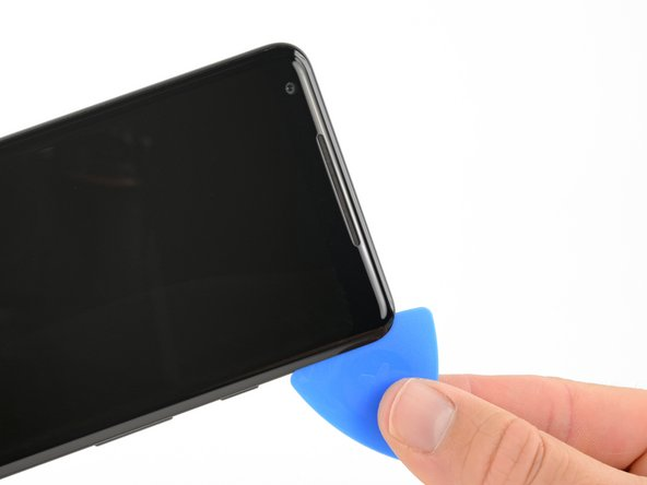 Reinsert the pick at the top-right corner of the phone, and slide it around the corner and along the top edge of the phone.