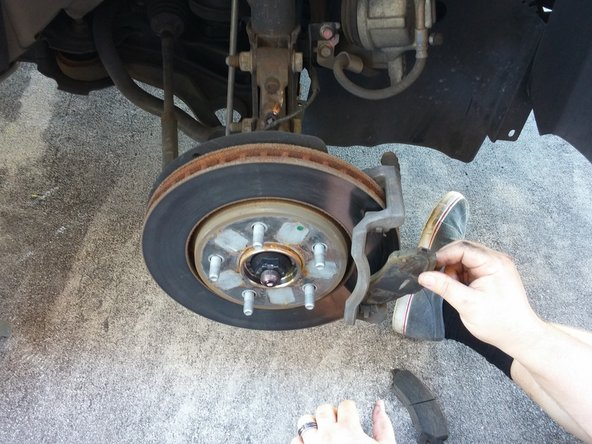 Remove the brake pads, being careful not to lose clips on caliper bracket.