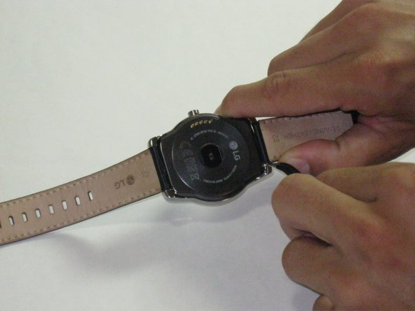 Image 1/2: Using '''tweezers''', remove the pins, one on each side, in order to only leave the face of the watch.