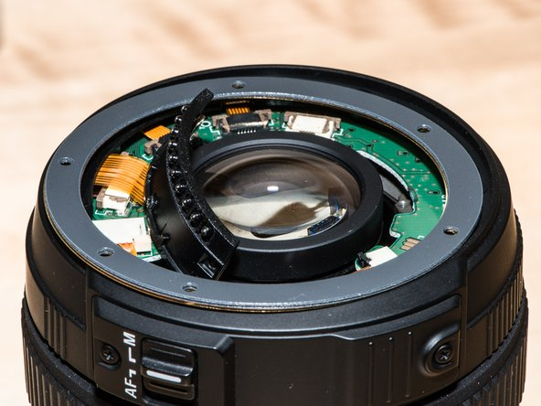 Drop on the mounting plate. The long leg goes inside the lens and into a hole in the central lens assembly; it's easy to see.
