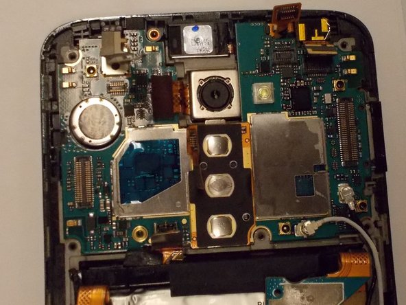 The motherboard is also held down with some adhesive but carefully can be pried up. Make use of Spudger.