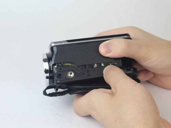 With both hands, pull the side strap apart from the rest of the camcorder.
