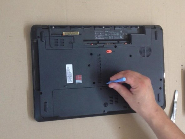 With a plastic tool remove the Memory RAM / Hard Drive / Wifi Cover Door