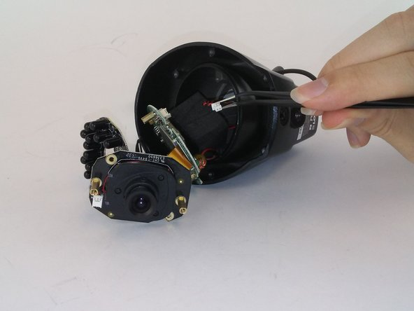 Use tweezers to disconnect the microphone wires from the internal components of camera.