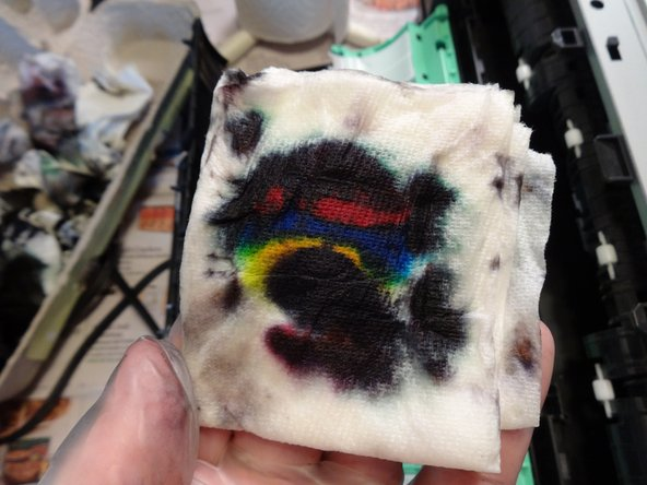 Put the print head on top of the paper towel and put a few drops of distilled water  for at least 15 minutes. This will soften the ink on the printhead.