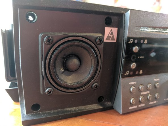 This device has a lot of screws and layers,  and some hidden tricks.  The first step is to pop off the speaker grilles, and remove just the top two screws.