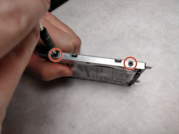 Using a JIS #00 screwdriver, unscrew the four 3 mm screws securing the hard drive to the enclosure.