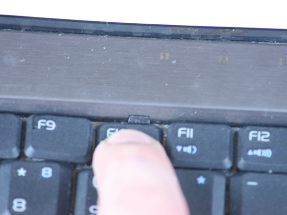 Image 1/3: Starting with the tab above the F1 key, press the tabs inward using your fingernail or spudger. Continue this process for the rest of the tabs.