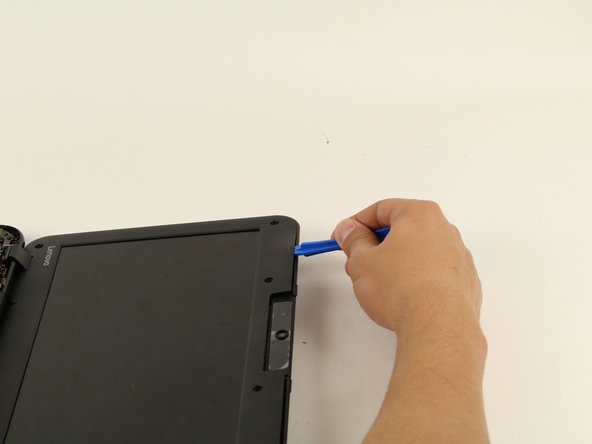 Image 2/2: While you run the plastic opening tool along the edge, several tabs will pop out.