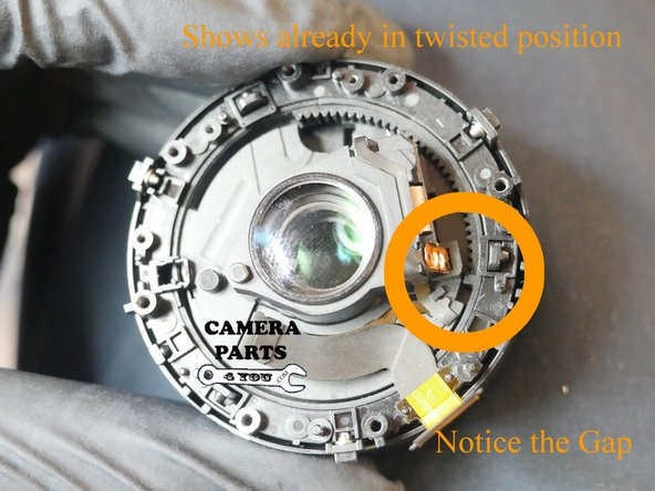 Shows already in twisted position. Now just pull up on the middle barrel (glass housing) until the lens mechanism starts to twist.