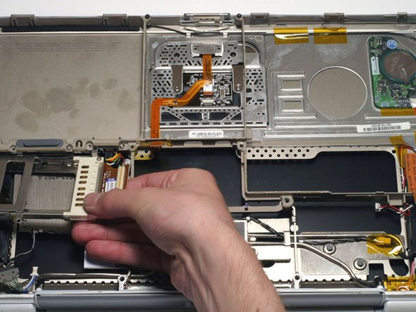 Remove the PC Card cage by pulling it to the right and twisting slightly toward you.