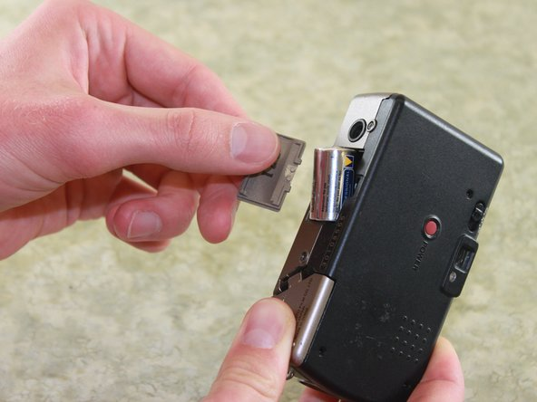 Remove the battery from the camera by pulling the battery door outward.