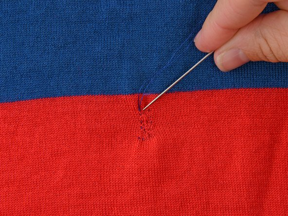 Insert the needle at a forty-five degree angle to your previous stitching, taking the needle under one row of the knit.