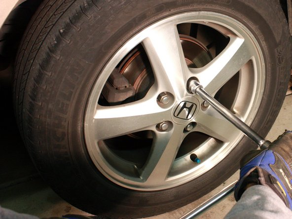 "Image 1/1: Using a ratchet attached to a 3/4"" socket, loosen wheel lug nuts. Do not remove them."