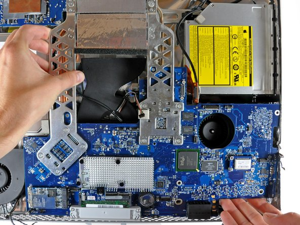 Carefully rotate the top edge of the logic board out of the rear case and lift the board up out of the iMac, minding the RAM arms and any cables that may get caught.