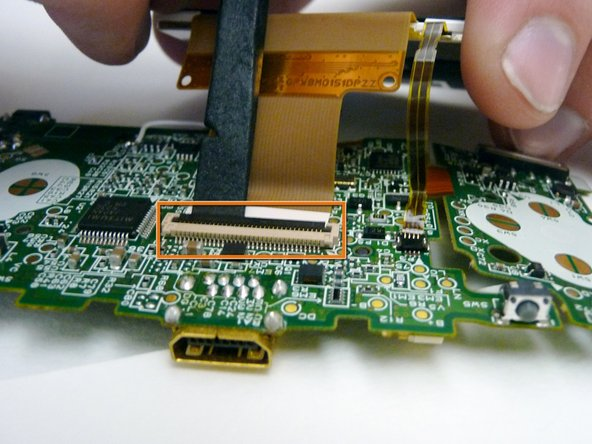 Image 2/3: Use a plastic spudger to disconnect the LCD's ZIF connector.