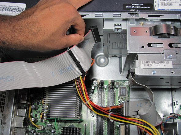 Grasp the cable and pull firmly to disconnect it from the optical drive.