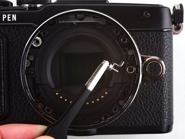 Image 2/3: Use tweezers to remove the spring underneath the lens hook.