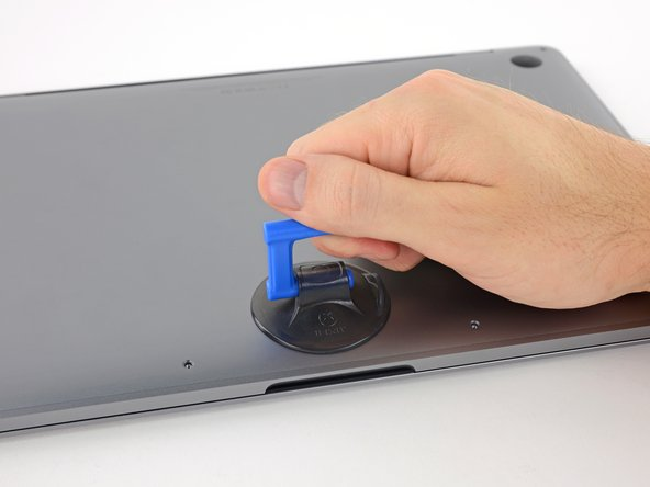 Apply a suction handle to the lower case near the front-center area of the MacBook Pro.