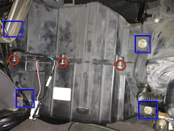 Image 1/3: Using a 10mm socket, remove four bolts (as indicated by the blue squares) The two on the right are easy to see but the two on the left are difficult to see and are behind structure.