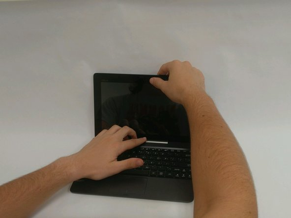 Remove the tablet portion of the device from the keyboard by pushing the large silver button near the base of the tablet. Pull up on the tablet to remove from the keyboard.