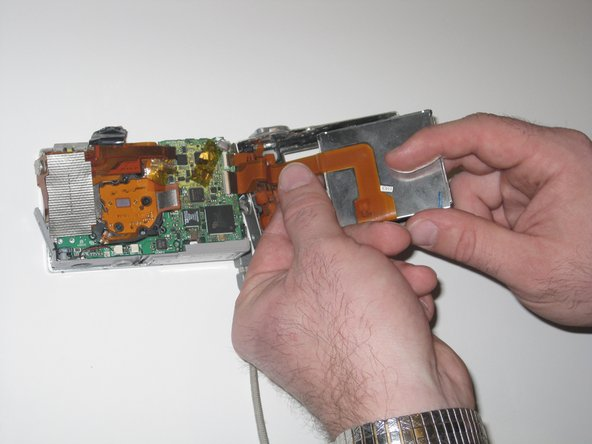Gently remove the LCD display data cable by gripping the end that is connected to the motherboard and pulling out.