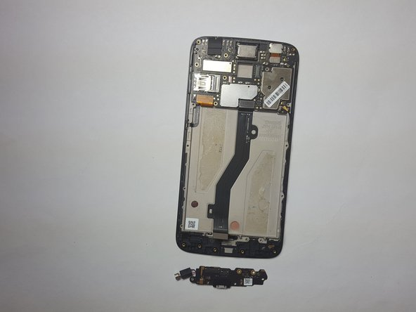 Use the Spudger to lift up and remove the Charging Port from the phone. The black box connected to the charging port will lift up with it. Remove the whole piece.
