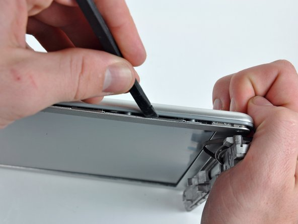 Insert a spudger between the right edge of the front display bezel and the plastic strip attached to the rear bezel, with the edge of the tool angled toward the LCD.