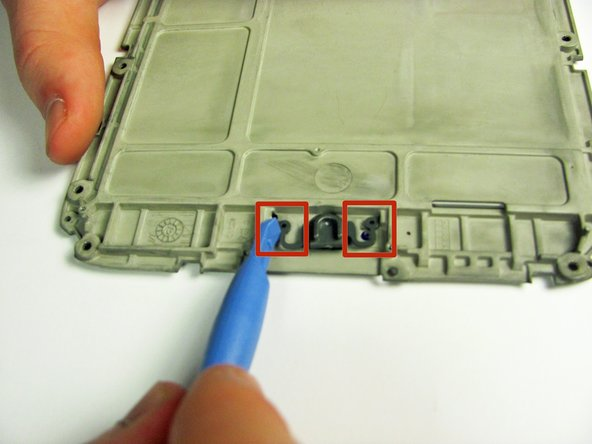 Using the plastic opening tool, lever the button arms towards the center of the nook so the button mechanism slides free.