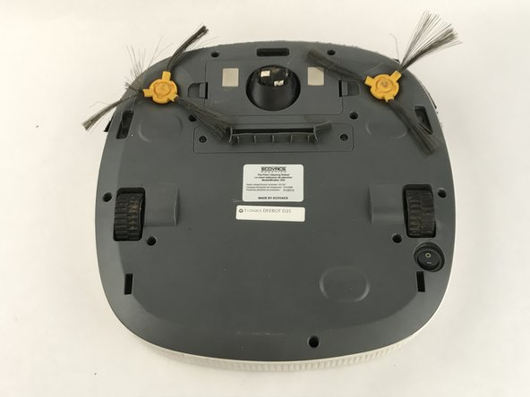Roll the Deebot over on a flat surface. The brushes will be located on the front with bright yellow connectors.