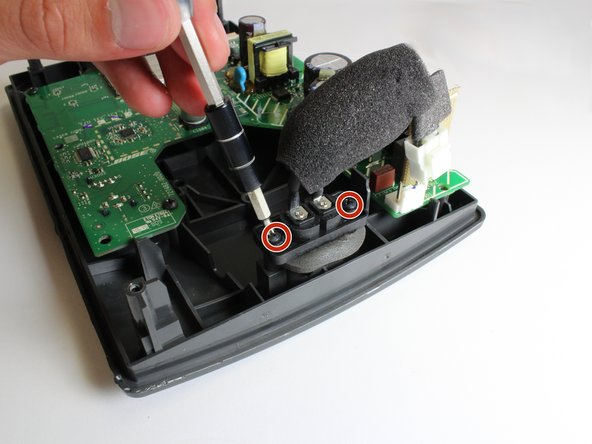 Use a #2 Phillips screwdriver to remove the two 15mm screws from either side of the charging port.