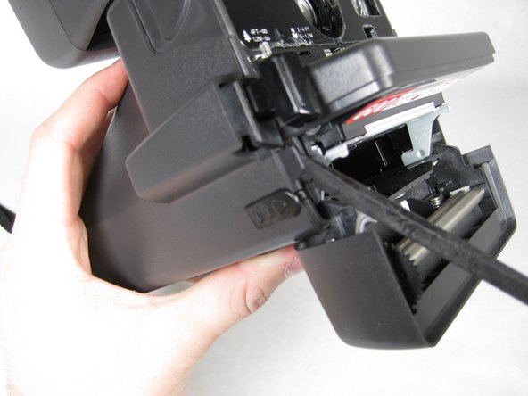 Insert spudger in between face of camera and sides where the four tabs are located.